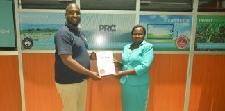 Brian Gacari, CEO PRC issuing s title deed to a happy client - Bizna